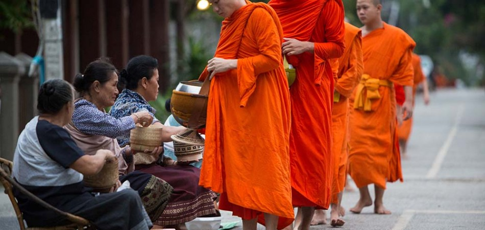 The tak bat, morning alms of Buddhist monks' morning collection of food in Luang Prabang